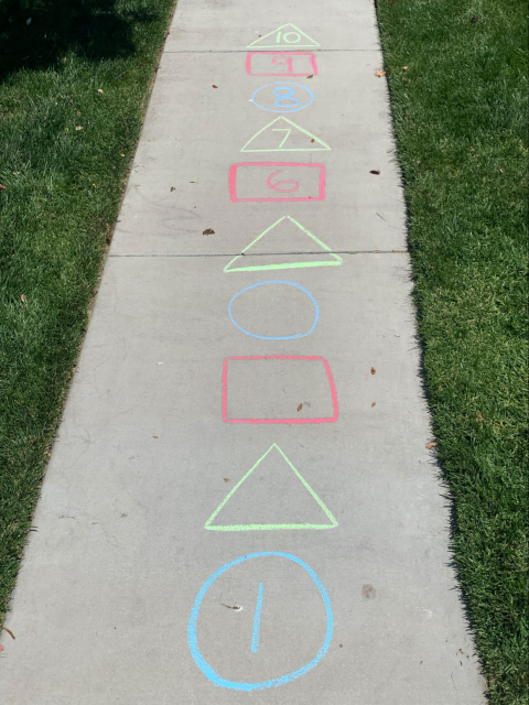 Sidewalk chalk shapes with numbers. Blue circle, 1. Green triangle, empty. Red rectangle, empty. Blue circle, empty. Green triangle, empty. Red rectangle, 6. Green triangle, 7. Blue circle, 8. Red rectangle, 9. Green triangle, 10.